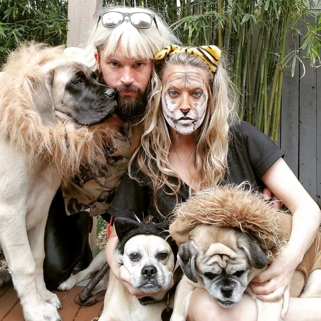 Dos fanáticos de Tiger King posan con sus tres perros en disfraces