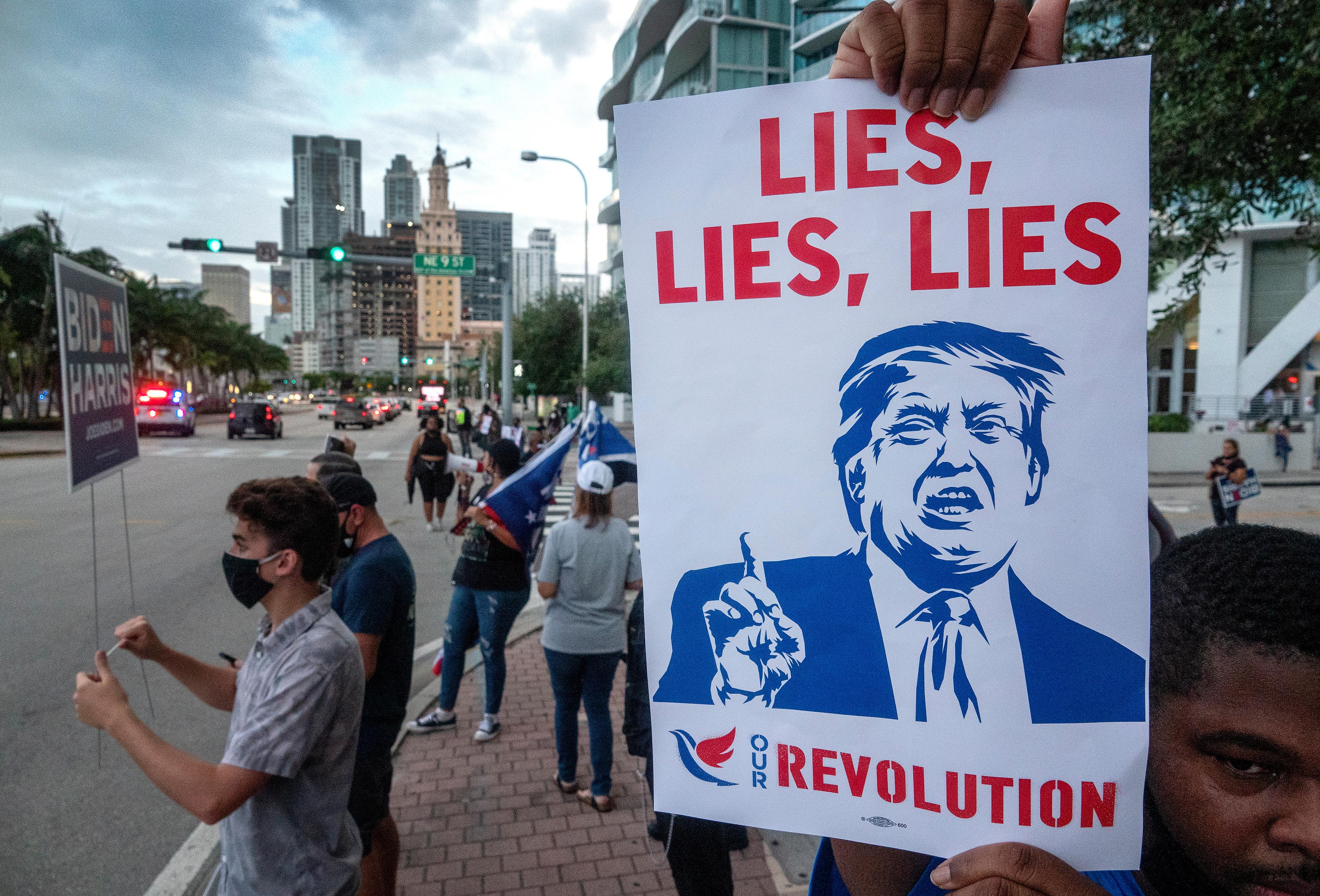 Los partidarios de Joe Biden llevan una pancarta que dice