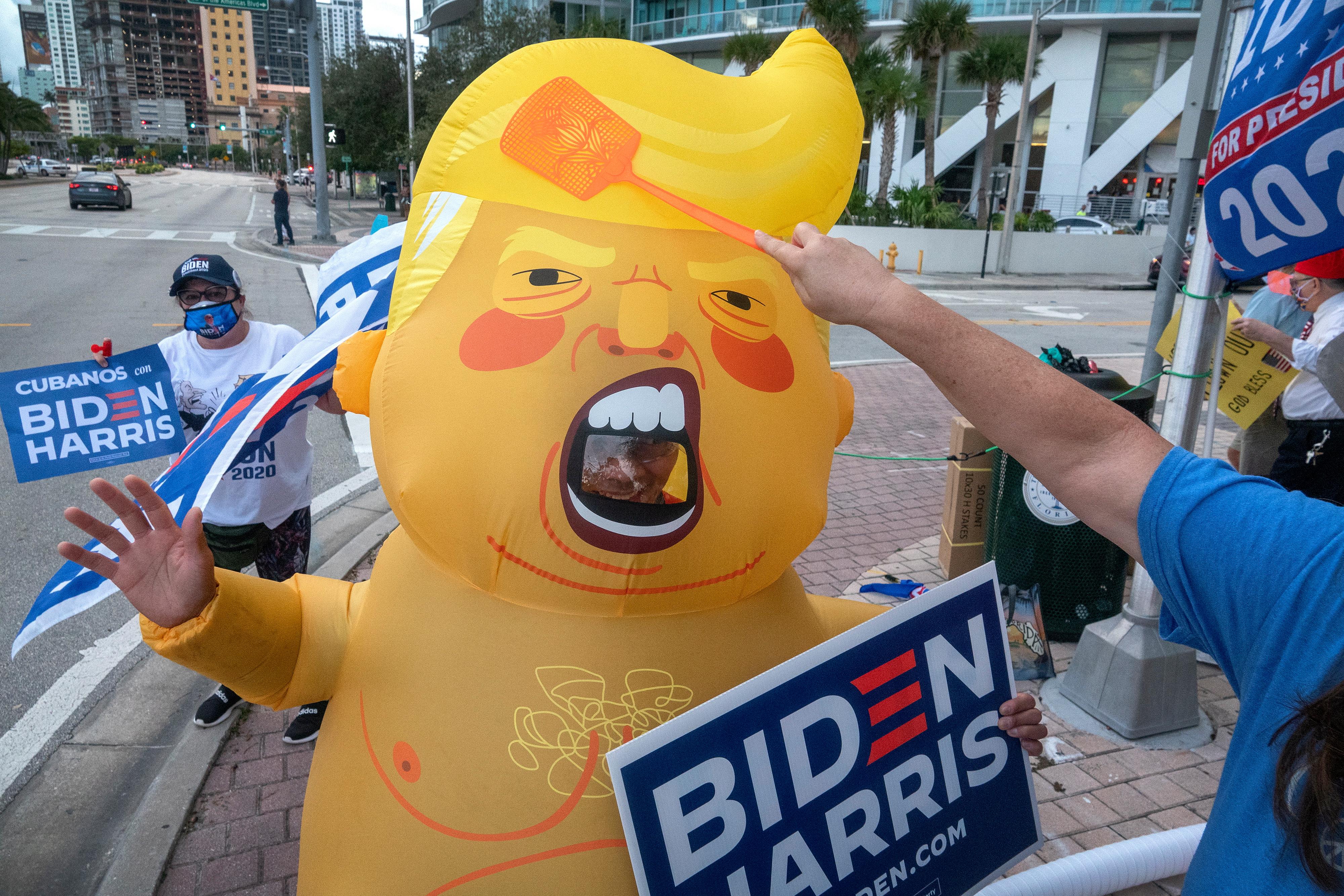 Fans de Joe Biden con hombre disfrazado de 'Trump Baby'