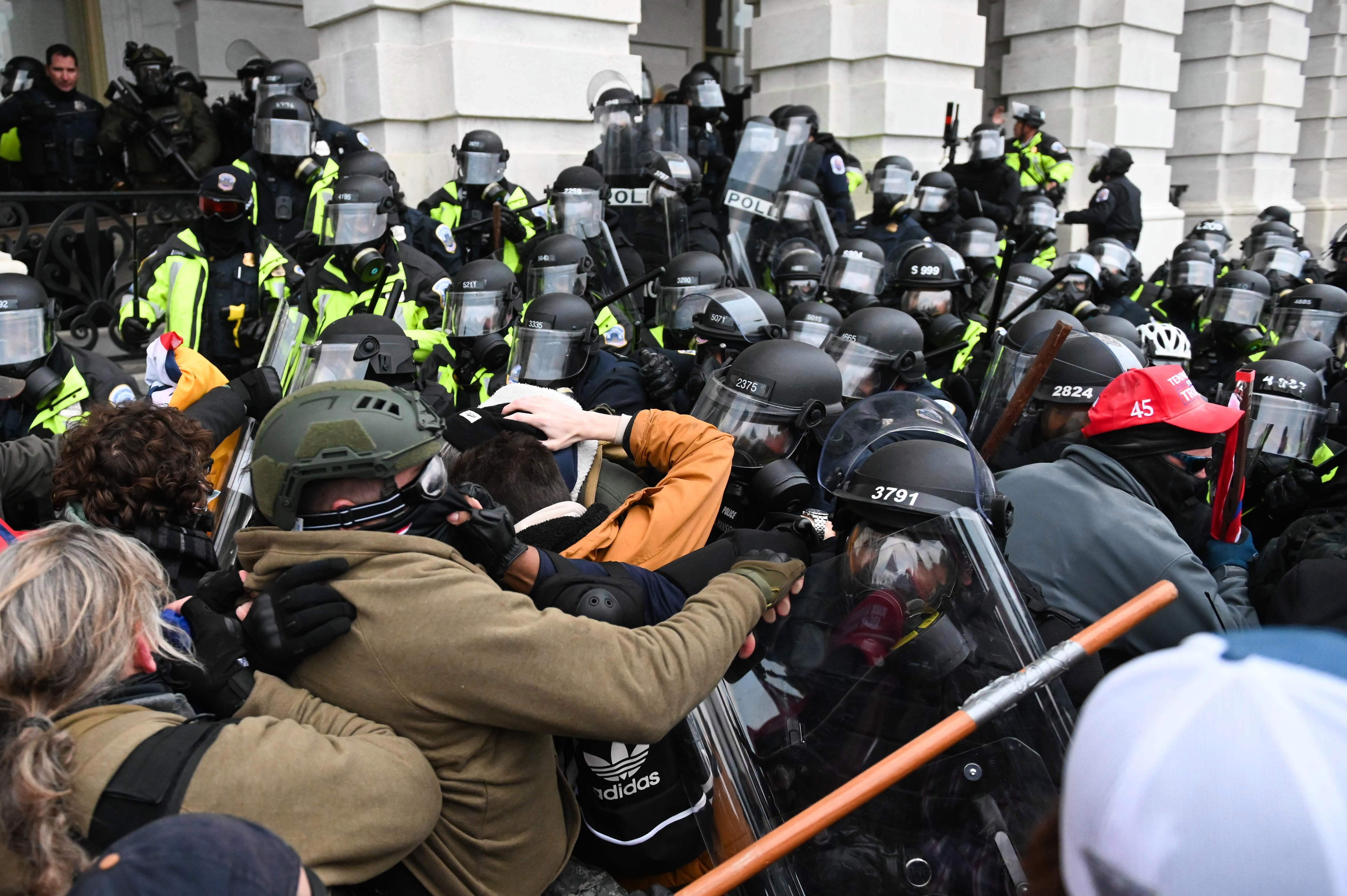 La policía antidisturbios intentó hacer retroceder a una multitud de partidarios del presidente Donald Trump después de asaltar el edificio del Capitolio el 6 de enero.